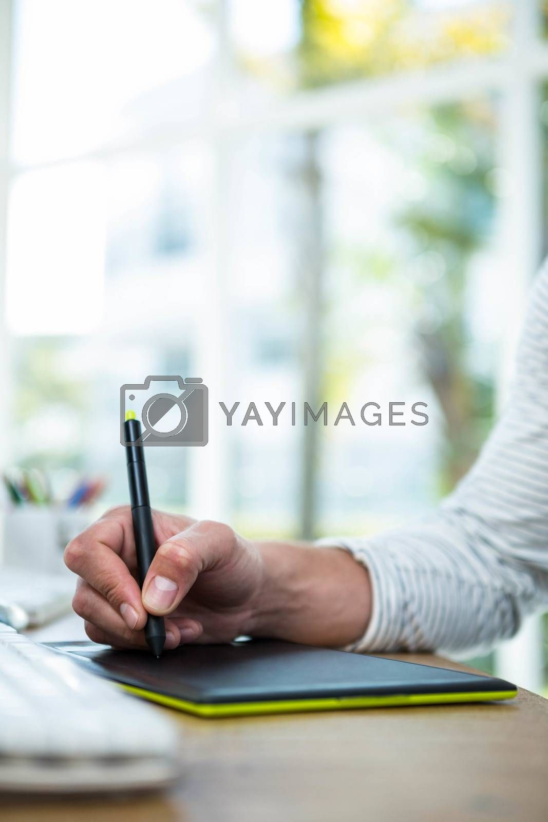 Masculine hands writing on digital tablet in a bright office