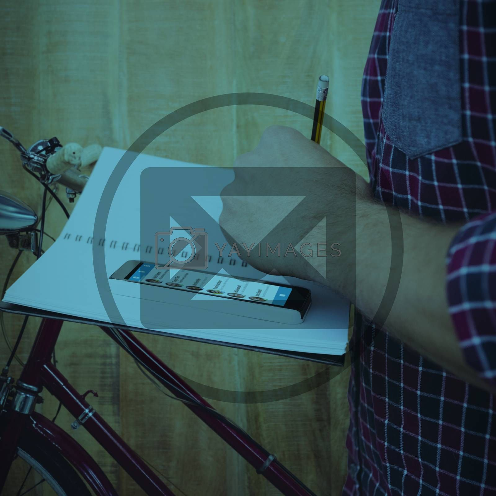 Cropped image of man with smartphone writing on book against close up view of a bicycle