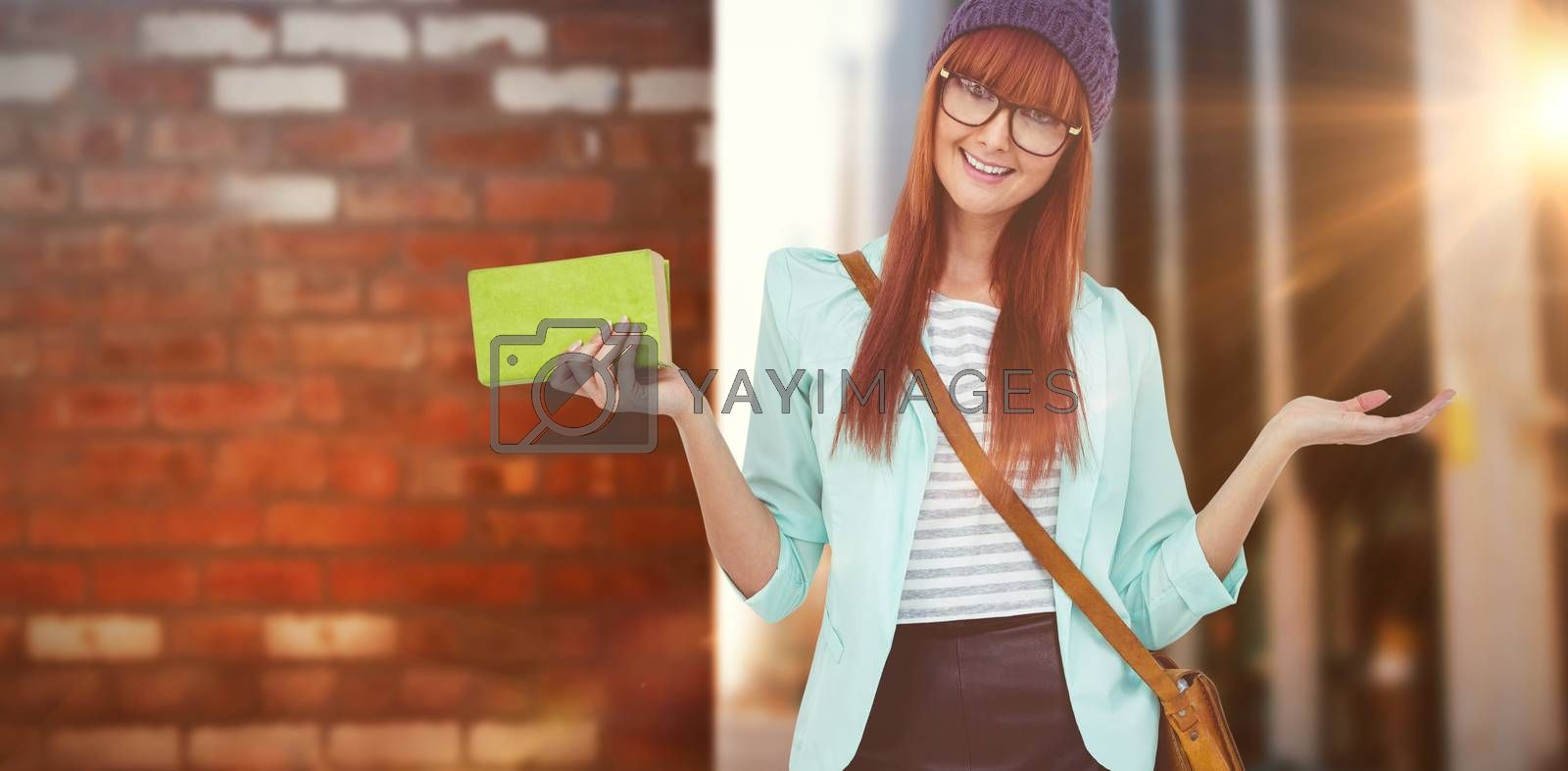 Smiling hipster woman with bag and book against wall of a house