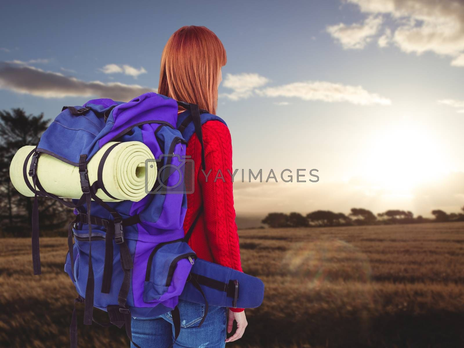 Smiling hipster woman with a travel bag against landscape of the countryside