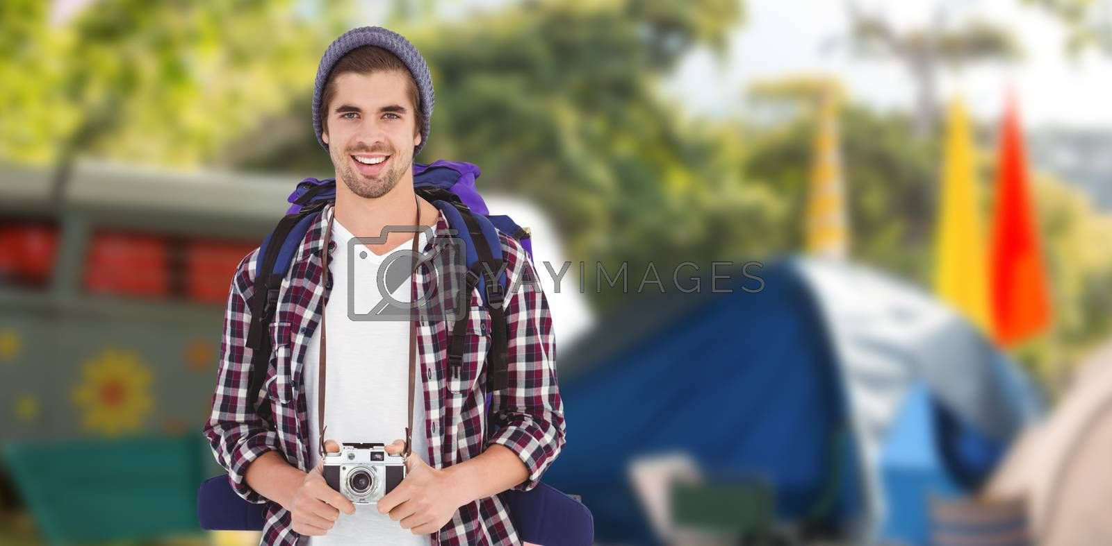 Portrait of happy man holding camera against empty campsite at music festival
