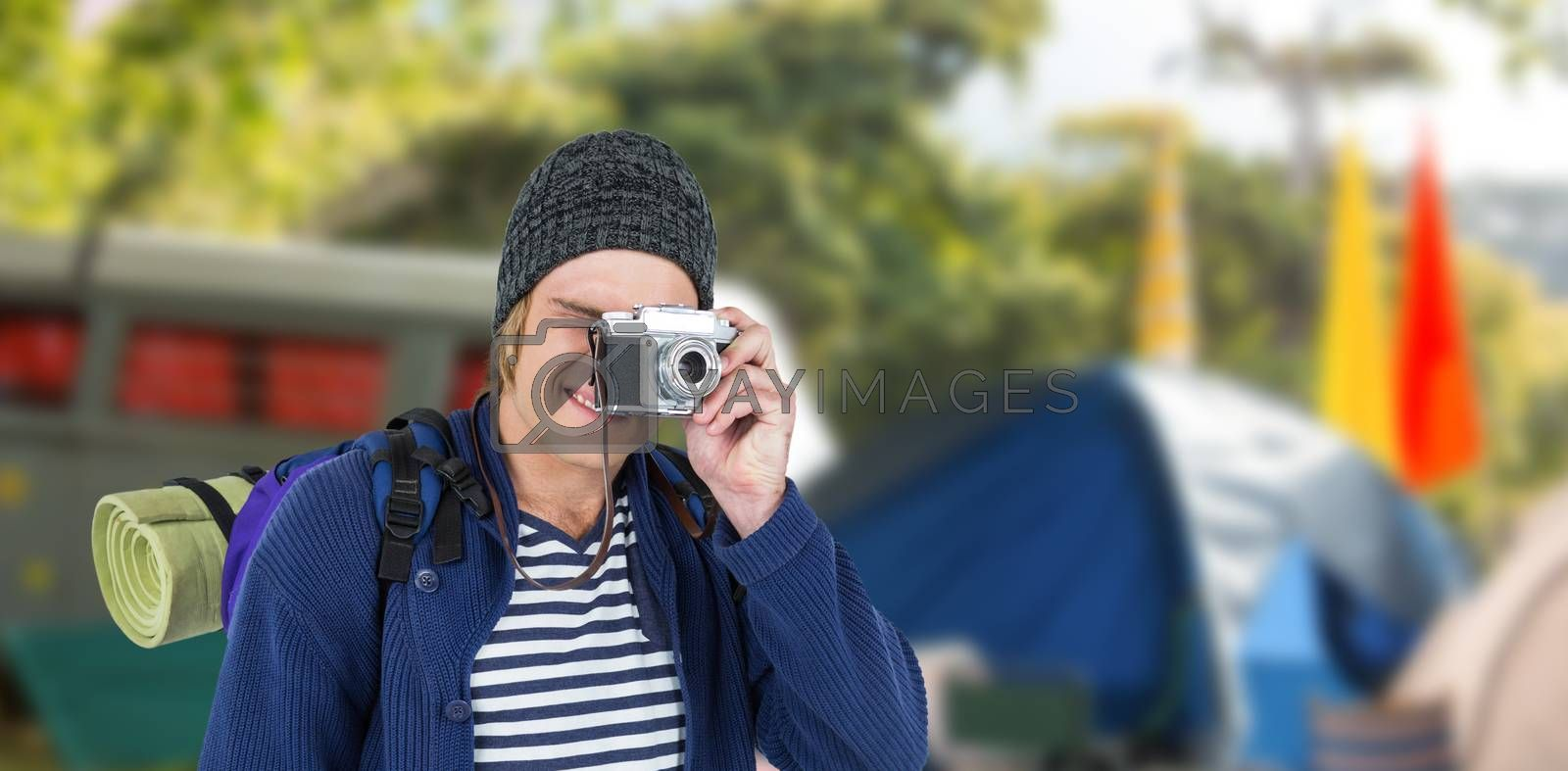Backpacker hipster taking pictures with a retro camera against empty campsite at music festival
