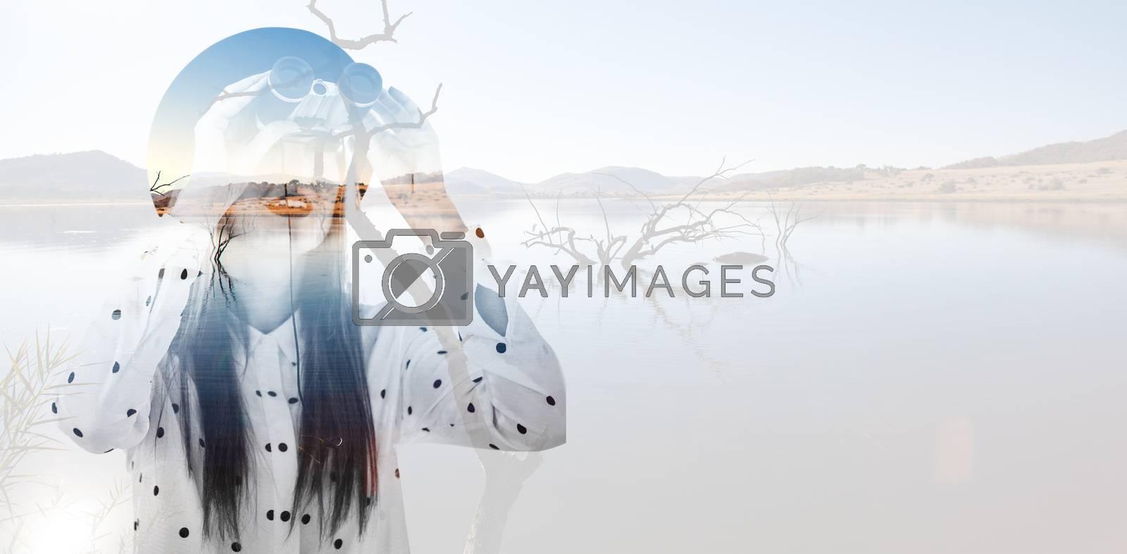 Smiling hipster woman using binoculars against lake