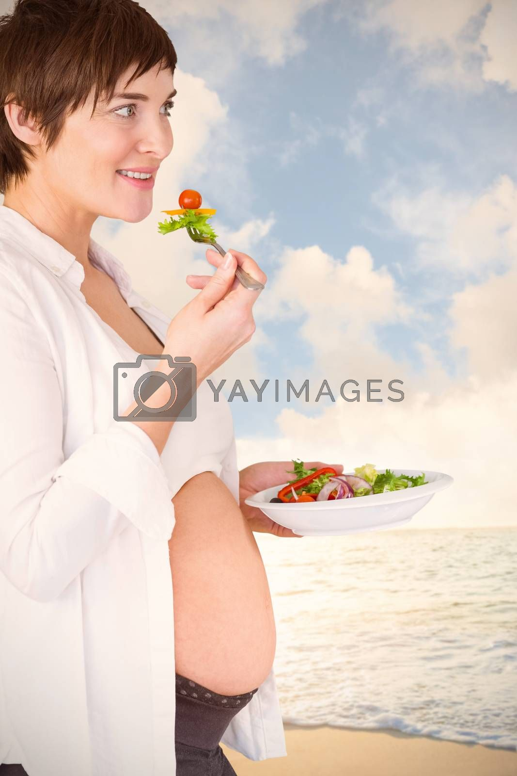Smiling pregnant woman having salad against surf board standing on the sand