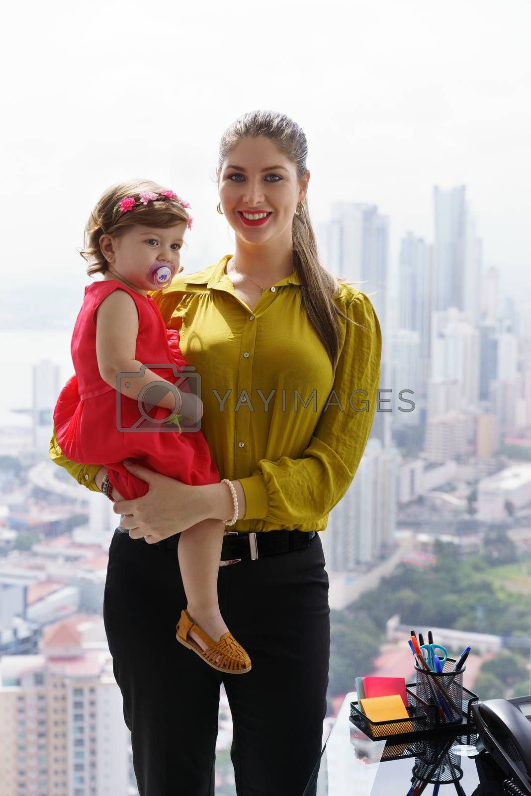 White businesswoman with little daughter in office. The executive mom spends time with her child and takes her at work