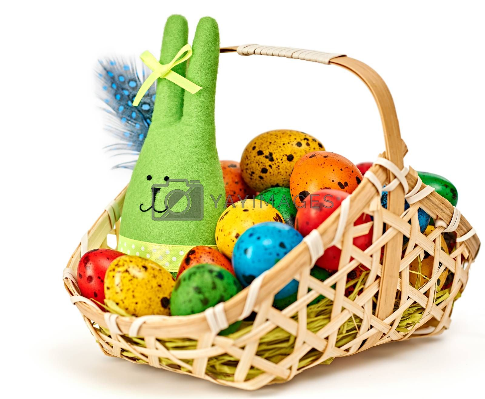 Easter rabbit and eggs in basket. Happy bunny handmade and hand painted multicolored quail eggs with straw and feathers, on white background. Unusual creative holiday greeting card