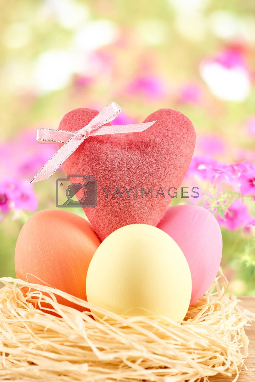 Easter eggs in in straw nest.  Hand painted decorated multicolored eggs and heart on floral background. Unusual creative holiday greeting card