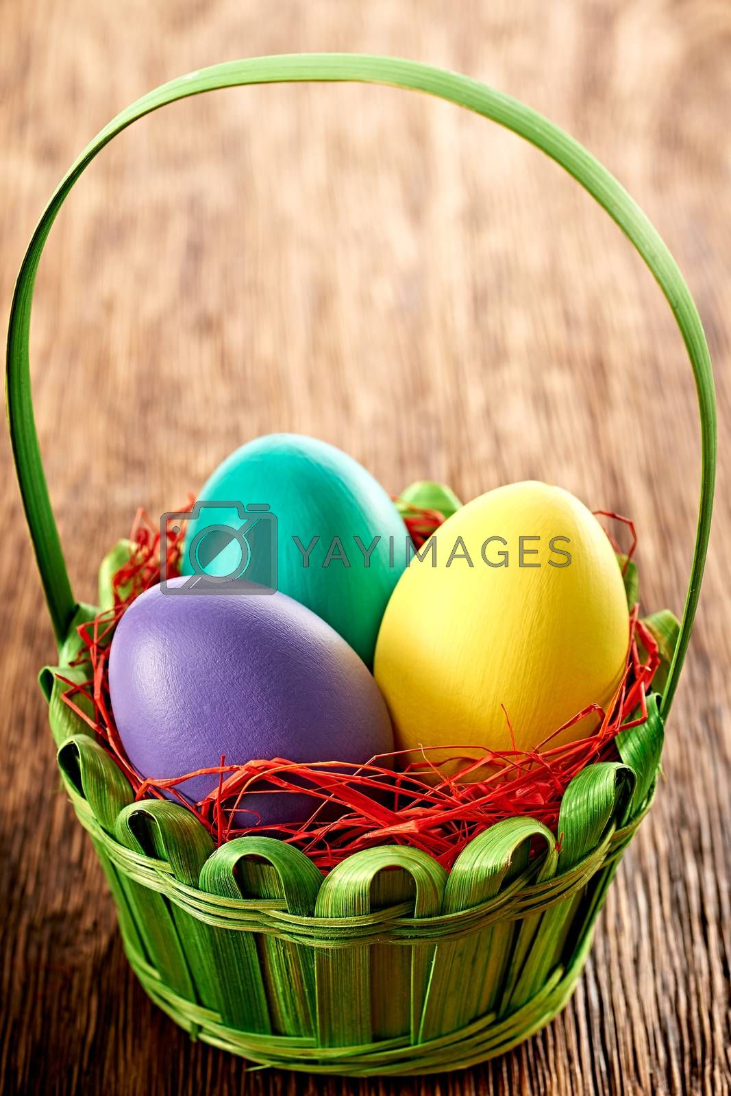 Easter eggs in green basket. Hand painted decorated multicolored eggs on wooden background. Unusual creative holiday greeting card