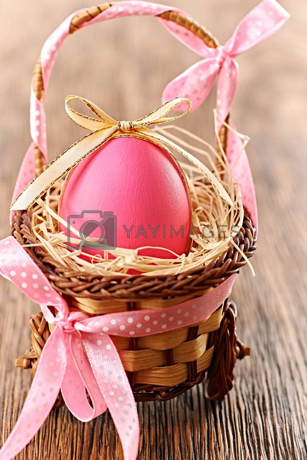 Easter egg in basket. Hand painted decorated pink egg with bow on wooden background. Unusual creative holiday greeting card