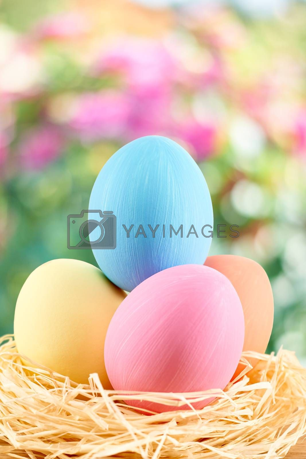 Easter eggs in in straw nest.  Hand painted decorated multicolored eggs on floral background. Unusual creative holiday greeting card