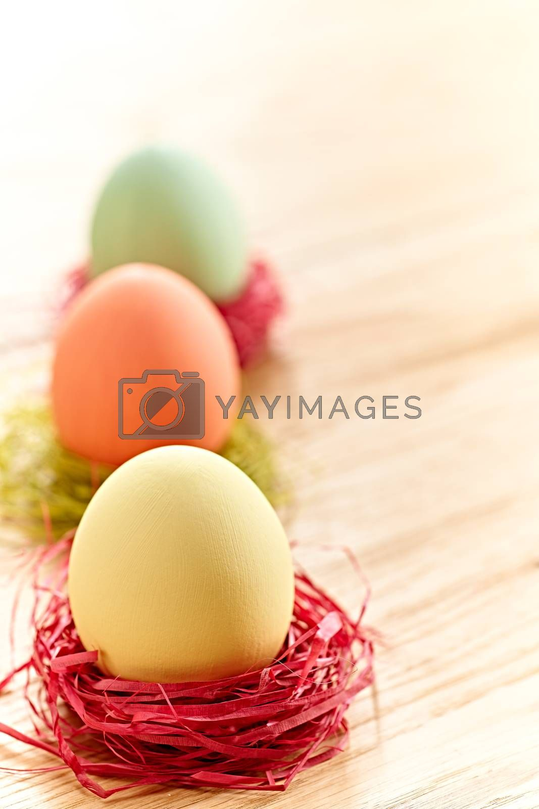 Easter eggs in nests. Hand painted decorated multicolored eggs with bow on wooden background. Unusual creative holiday greeting card