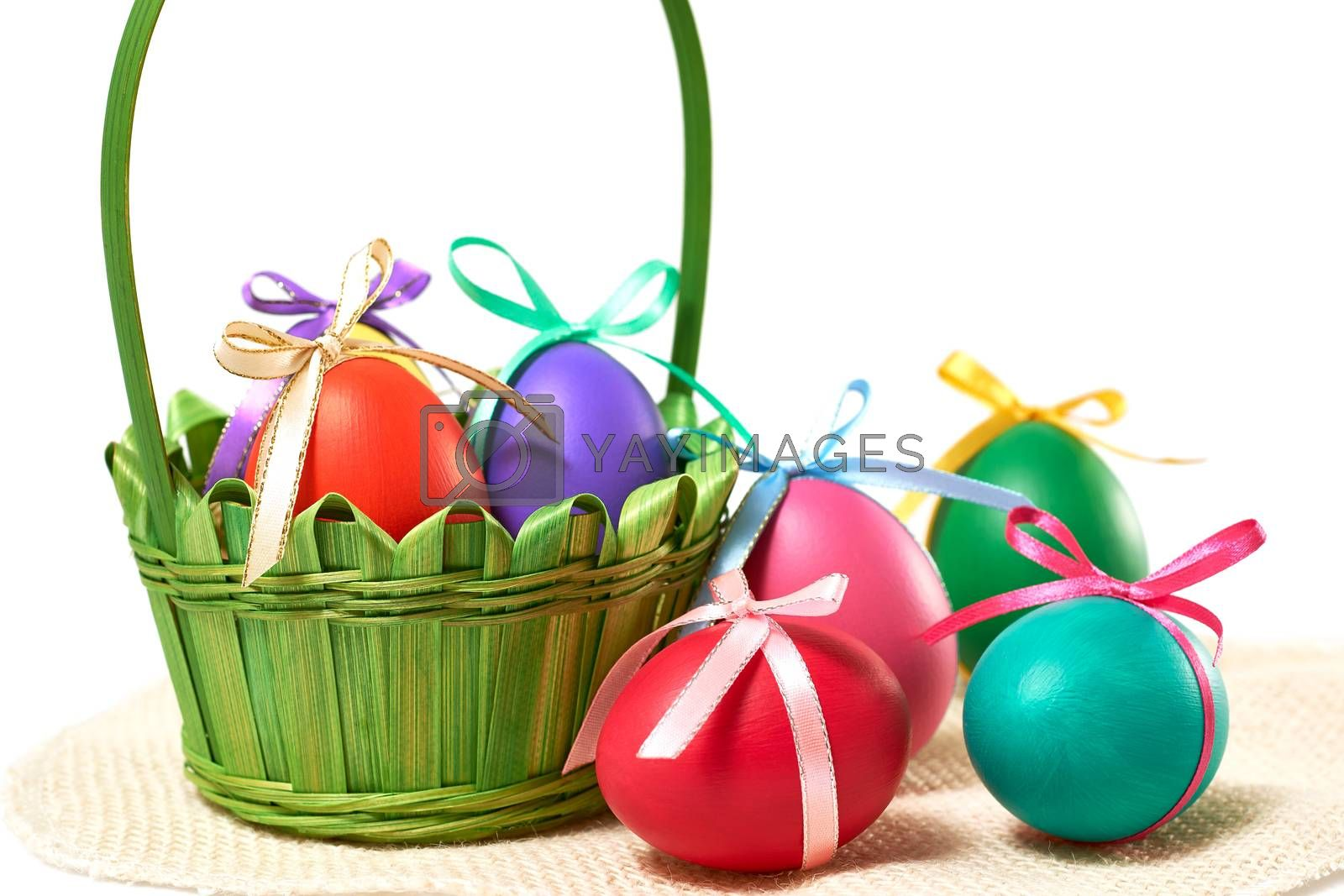 Easter eggs in green basket. Hand painted decorated multicolored eggs on white background. Unusual creative holiday greeting card