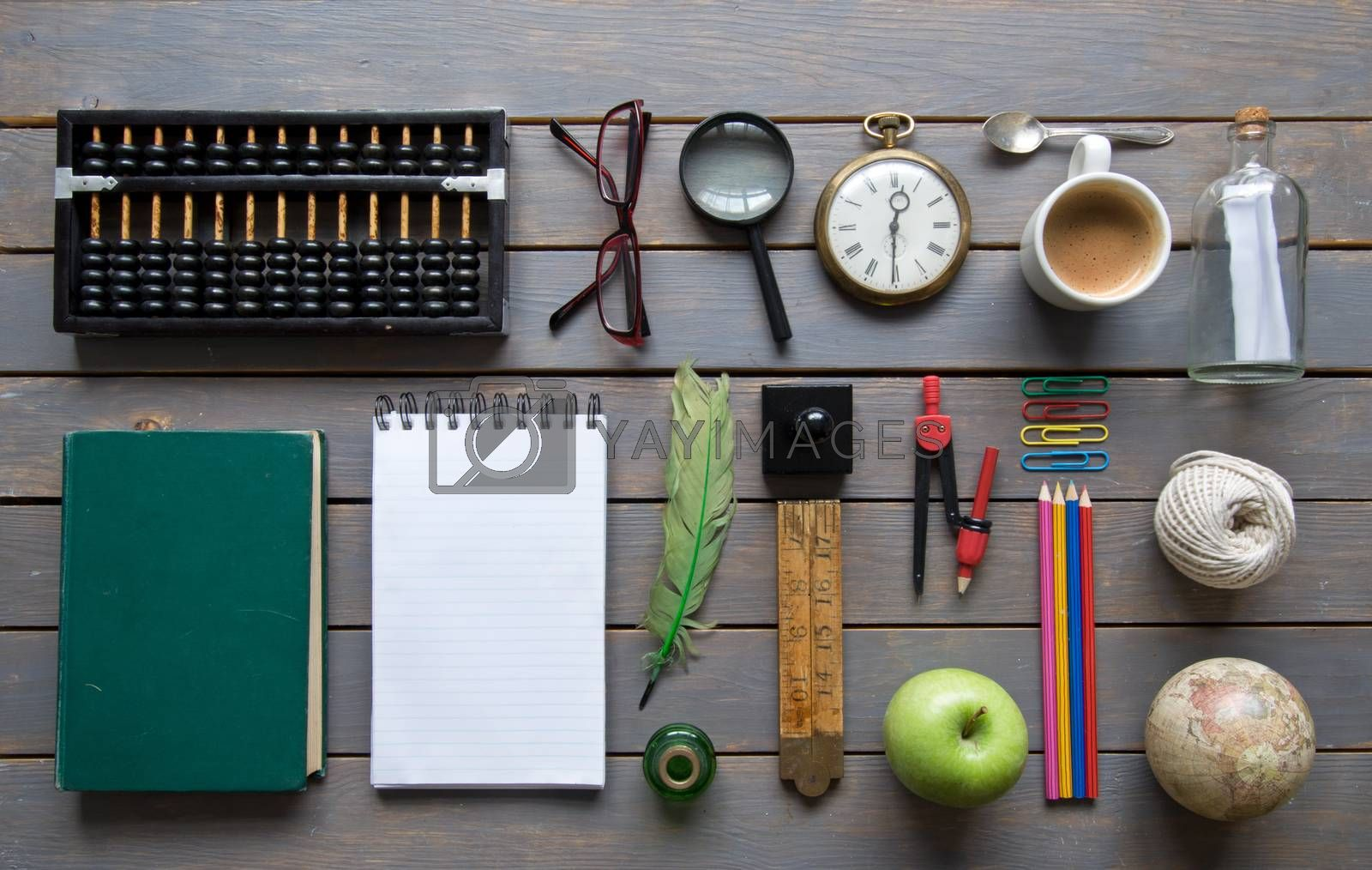 Various items, including stationery and vintage,  laid out on a wooden background