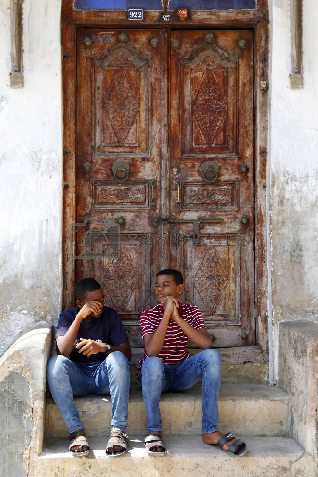 Stone Town, Tanzania - December 30, 2015: Two young people sitting on the steps in the background a traditional wooden door in Stone Town, Zanzibar