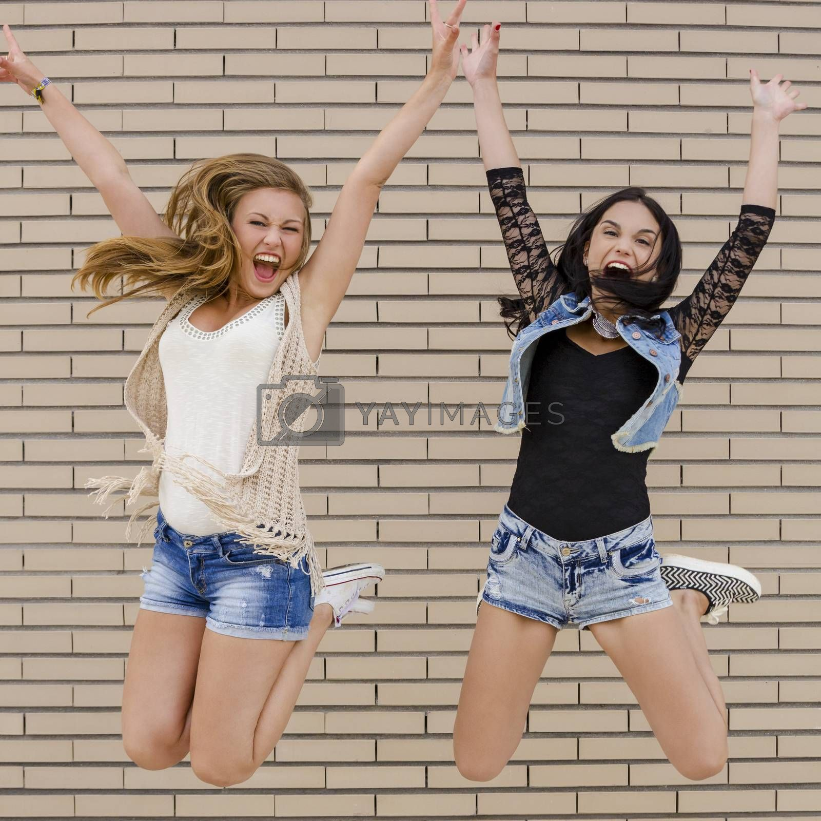 Two beautiful and young jumping in front of a brick wall