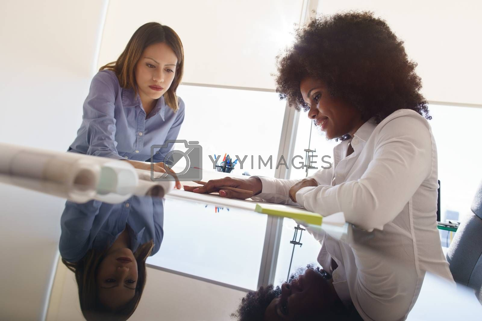 Team of two female architects, sitting at desk in office. The women talk reviewing a building plan. Reflections on table