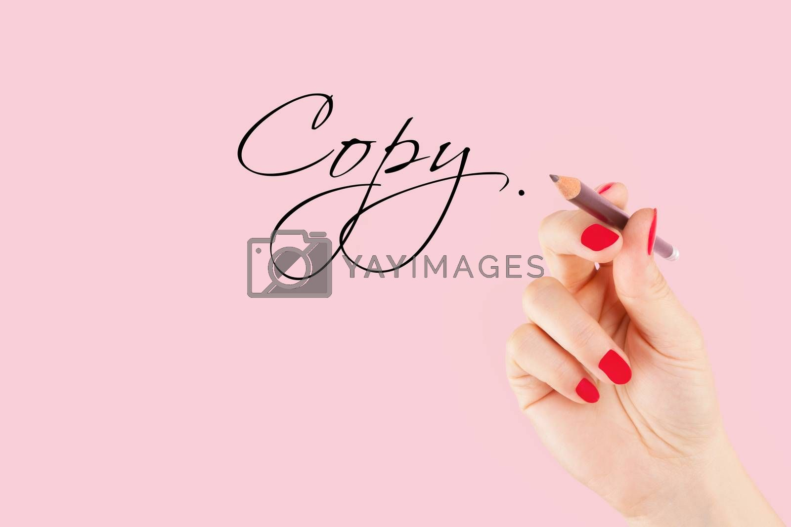 Creative industries. Female hand with pencil writng the word copy in caligraphy. Copy writing.