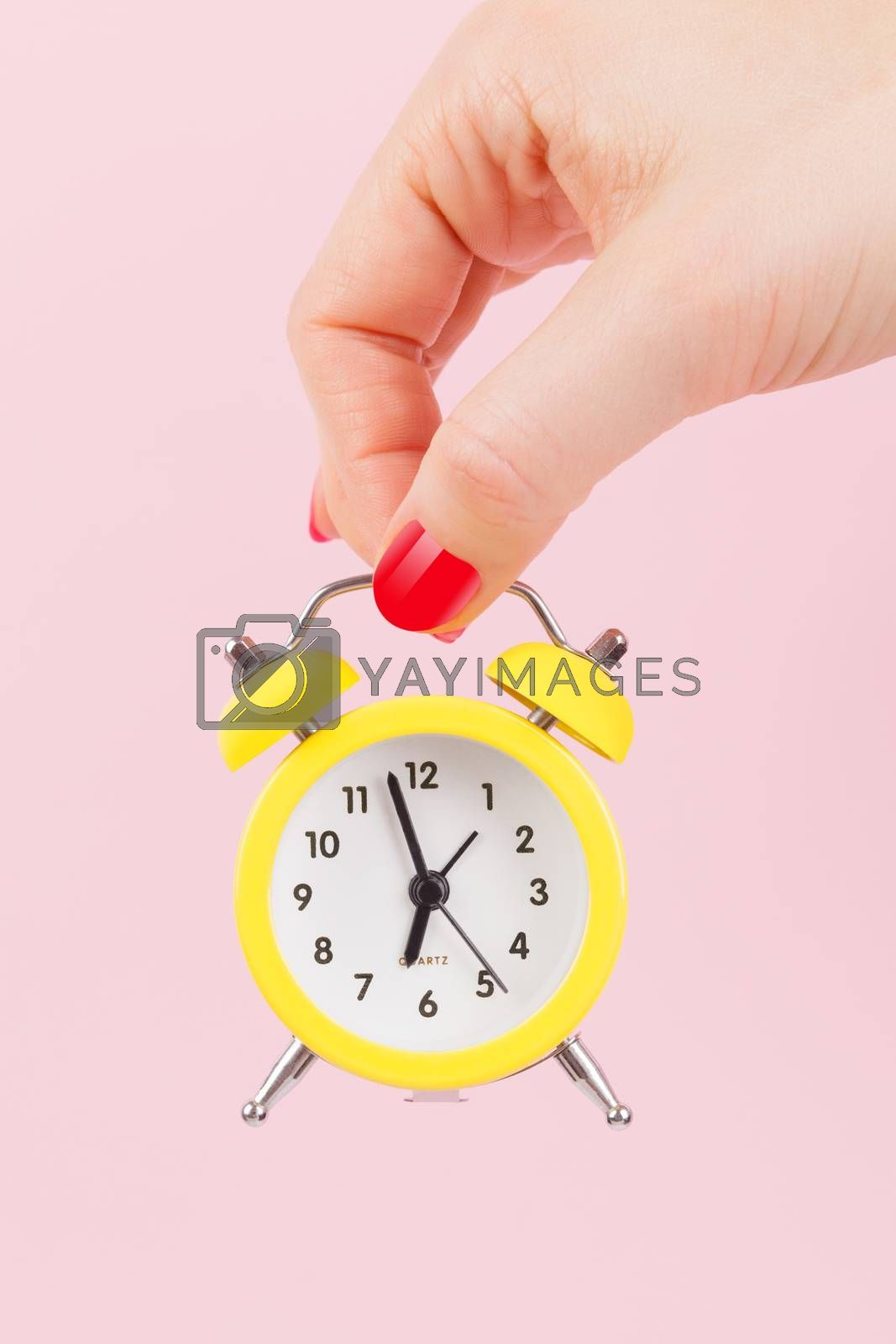 Female hand with yellow alarm clock on pink background. Deadline. Running late. Just in time. Time concept.