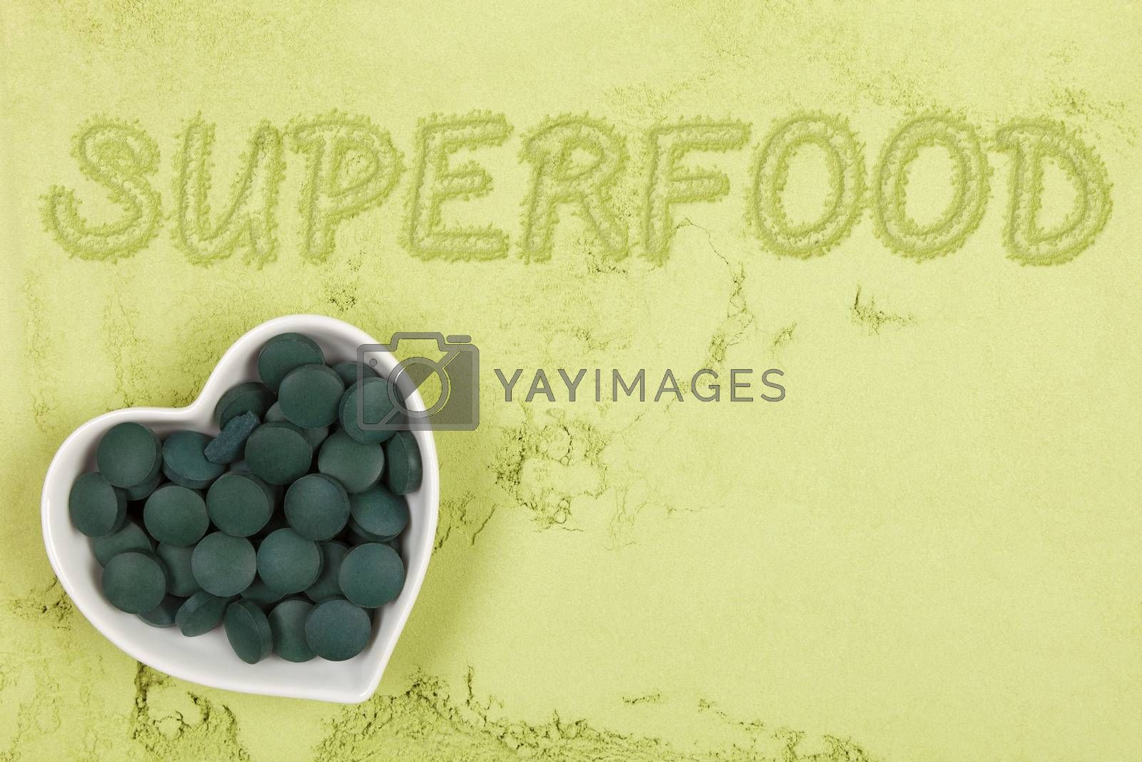 Green food supplement. Word superfood written in green ground powder, top view. Healthy lifestyle.