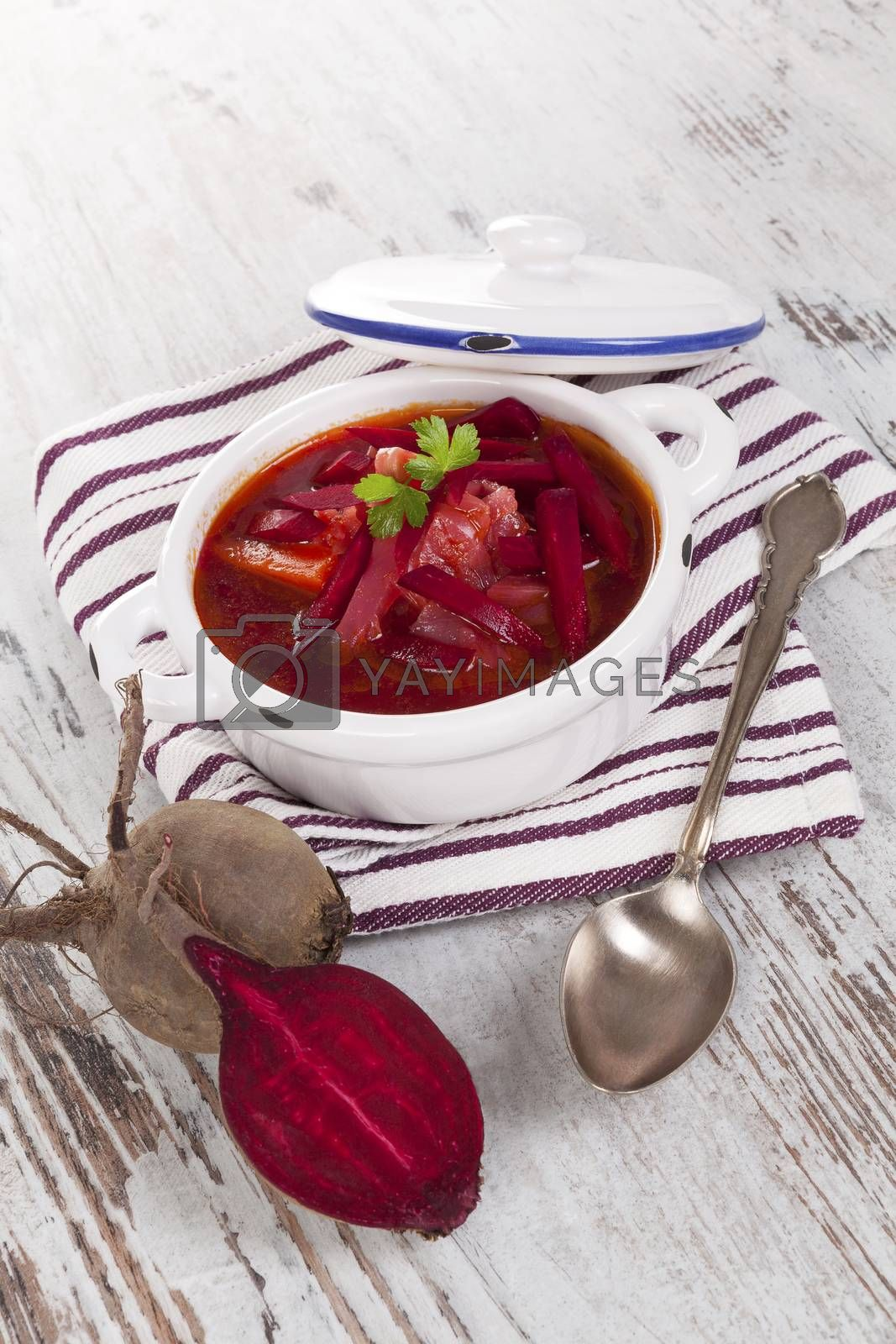 Delicious ukrainian borsch soup on white wooden background. Culinary food eating.
