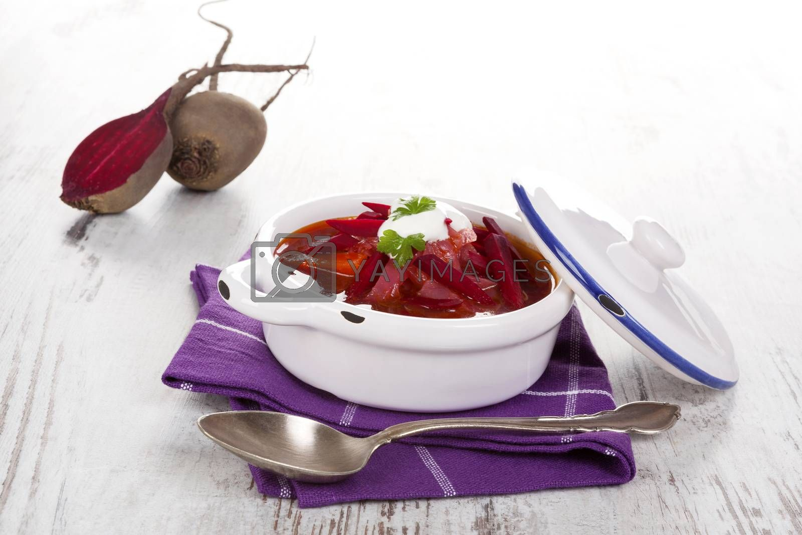 Delicious ukrainian borsch soup with fresh beetroot vegetable on purple cloth on rustic wooden table. Traditional european cuisine.