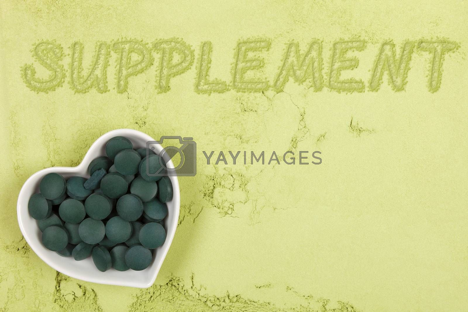 Dietary supplement. Green food supplement. Word supplement. written in green ground powder, top view. Healthy lifestyle.