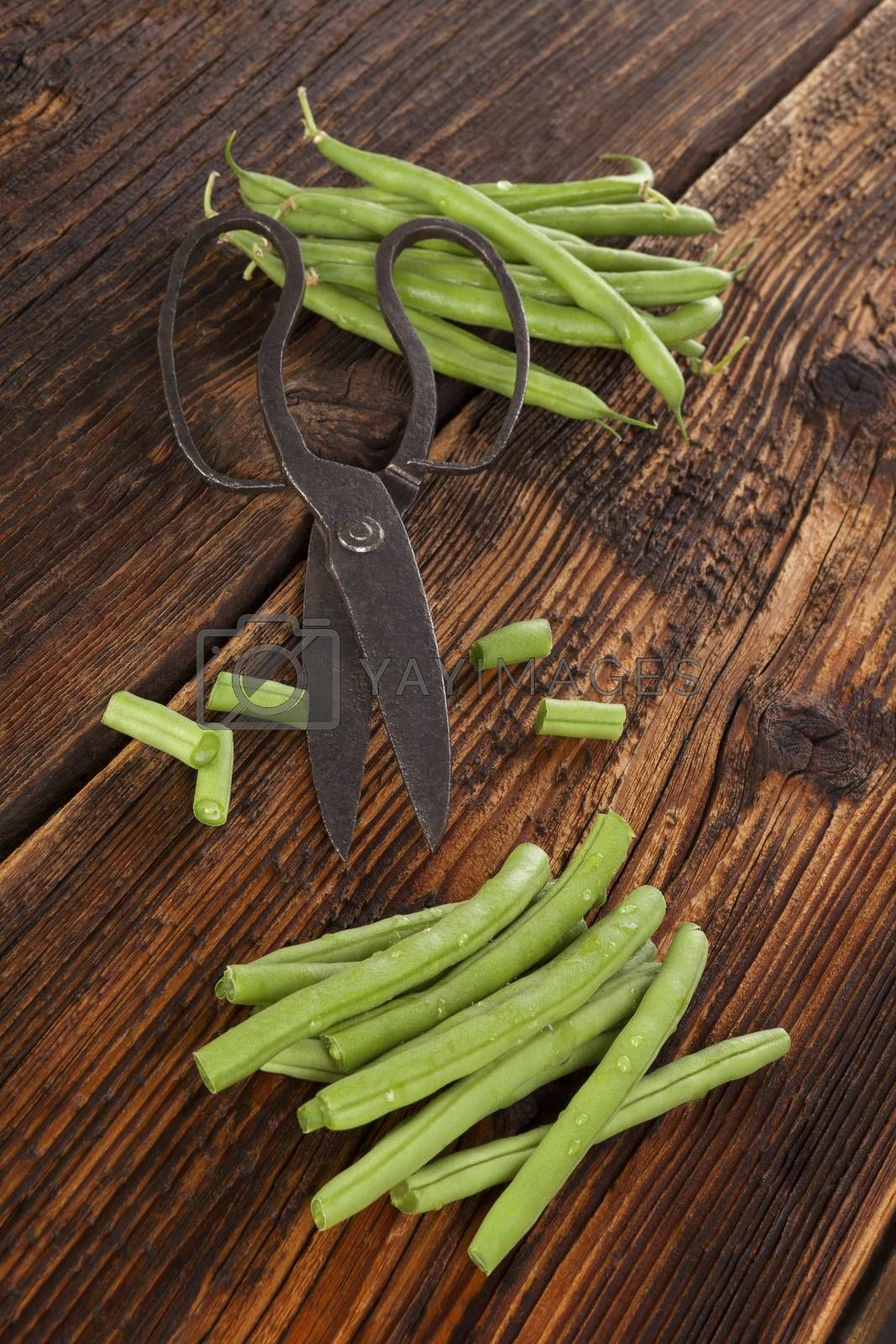 Raw fresh green beans with water drops on brown wooden textured table. Fresh vegetable eating.