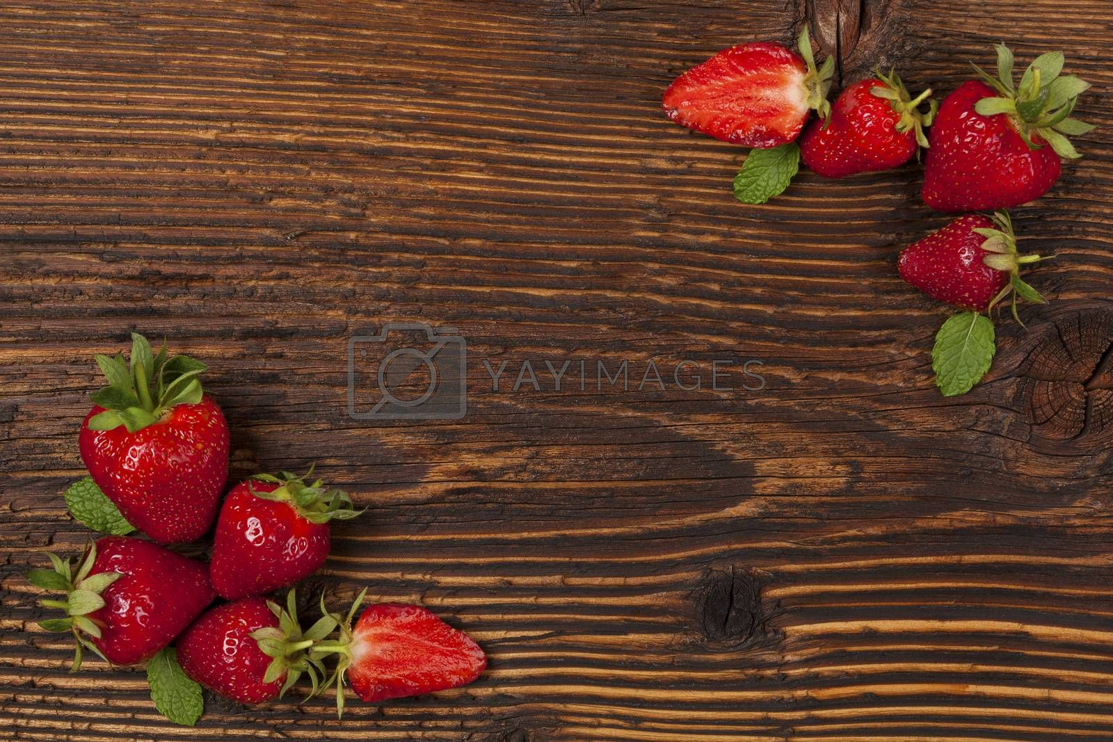 Ripe strawberries on rustic wooden brown table, flat lay. Strawberry background with copyspace. Healthy fruit eating.
