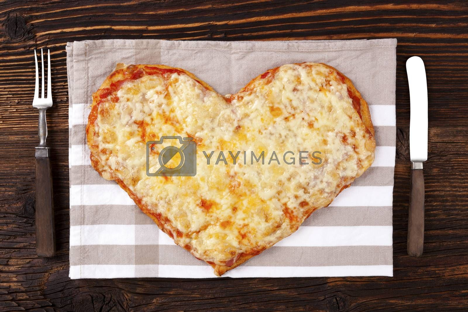 Delicious pizza in heart shape on wooden table, top view. Culinary pizza eating. I love pizza.