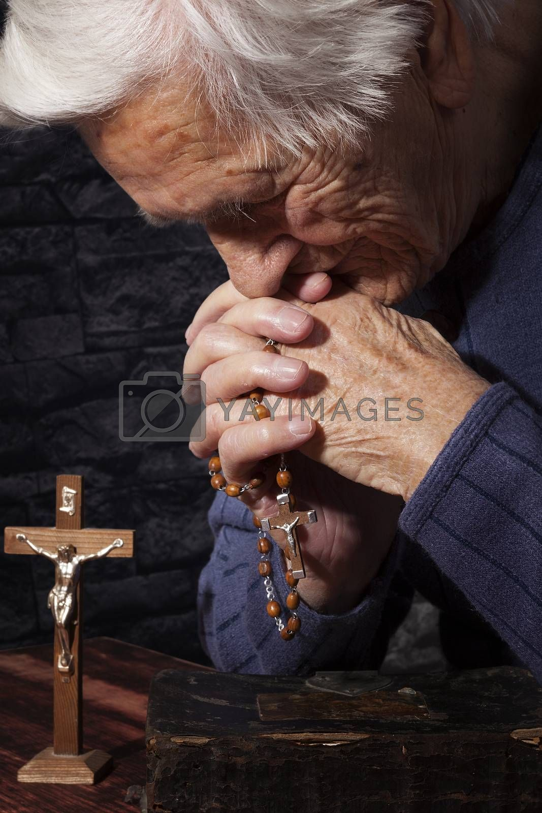 Grandmother praying. Old wrinkled beautiful woman praying with rosary. Faith, spiritualy and religion.