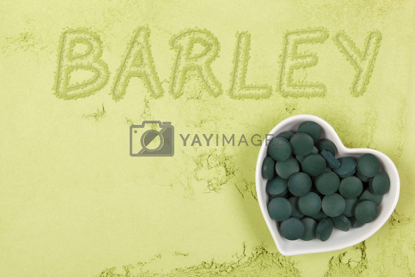 Green food supplement. Word barley written in green ground powder, top view. Healthy lifestyle.