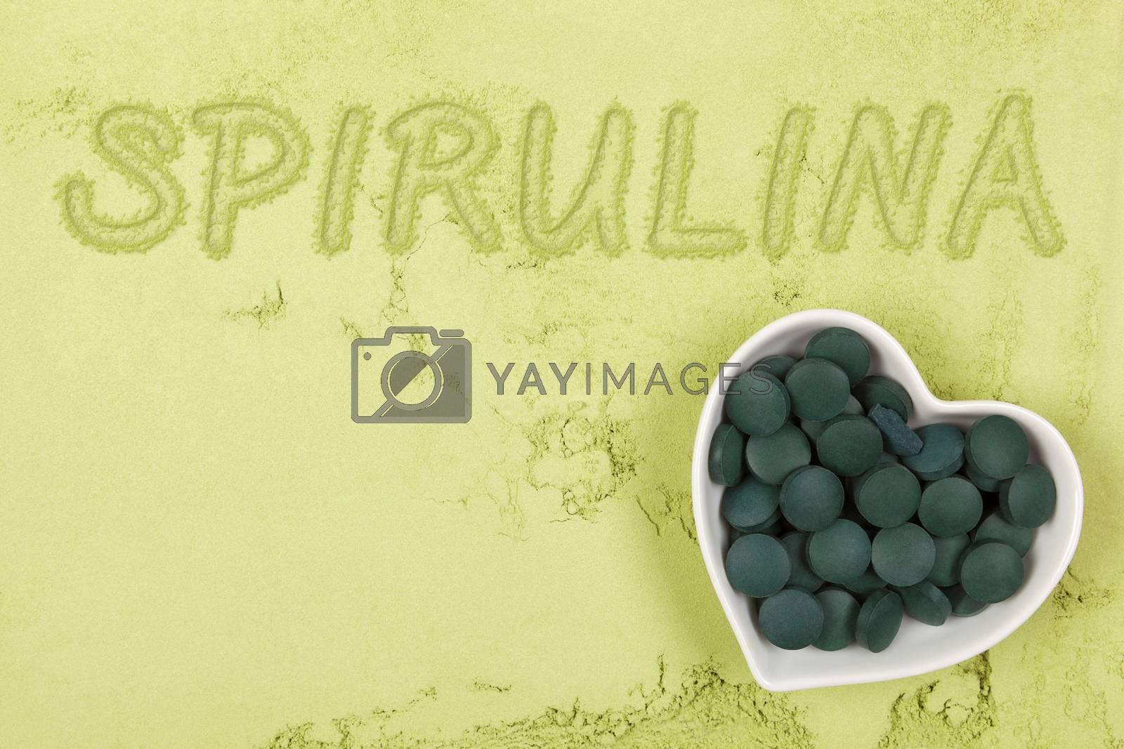 Spirulina. Green food supplement. Word spirulina written in green ground powder, top view. Healthy lifestyle.