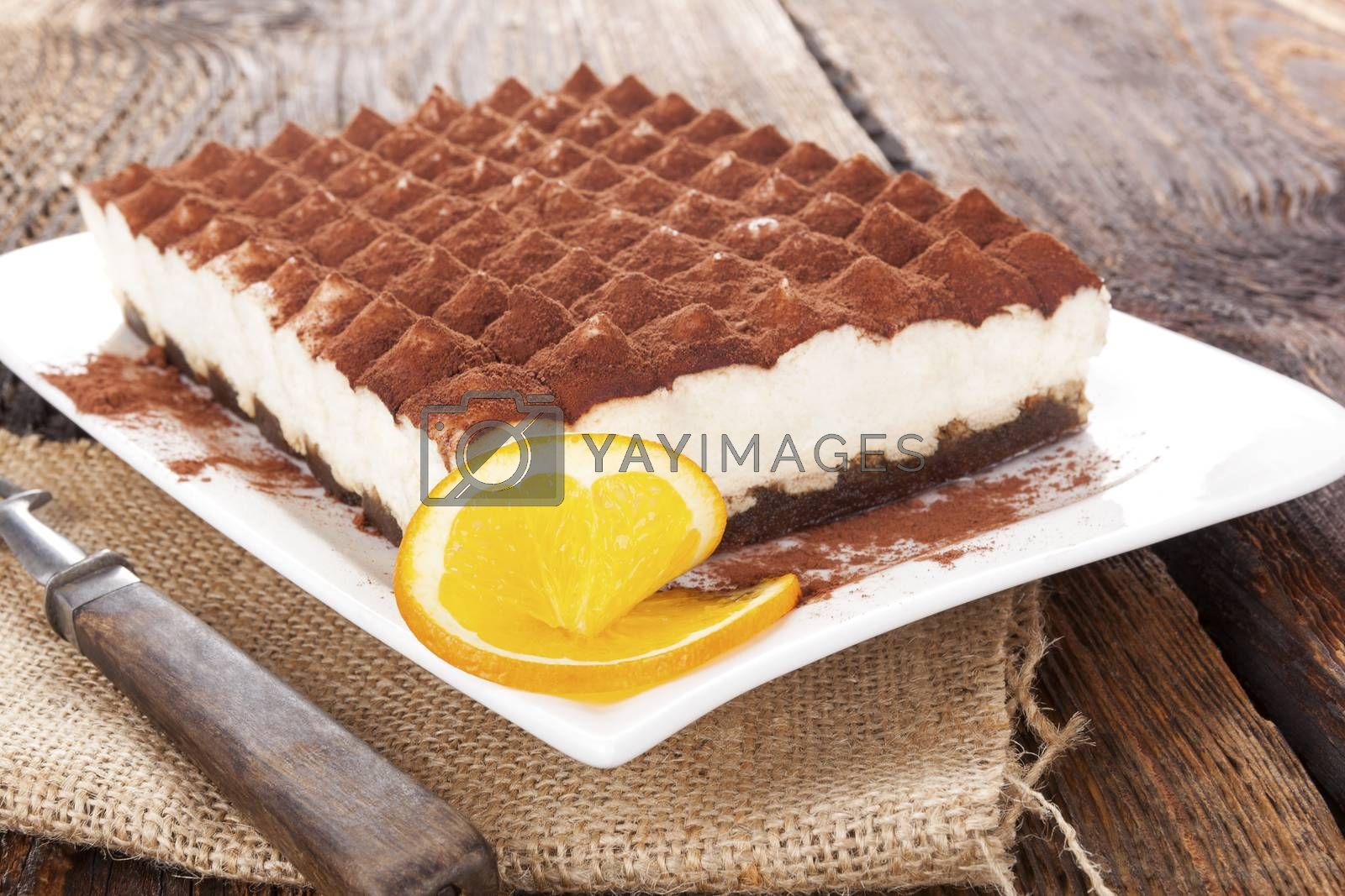 Delicious tiramisu dessert on brown wooden table. Culinary traditional sweet dessert.