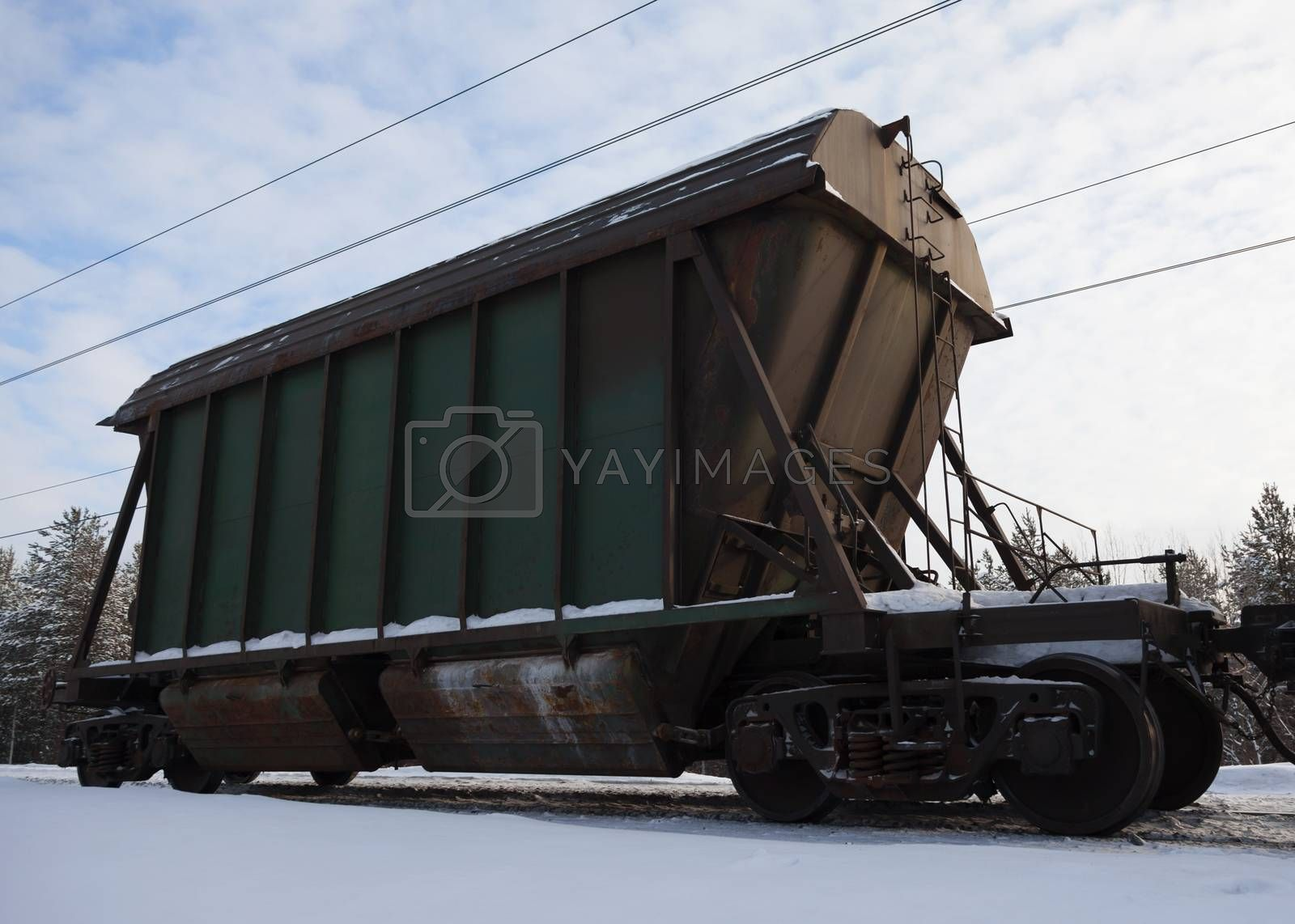 The last car of a freight train on the background of white snow.