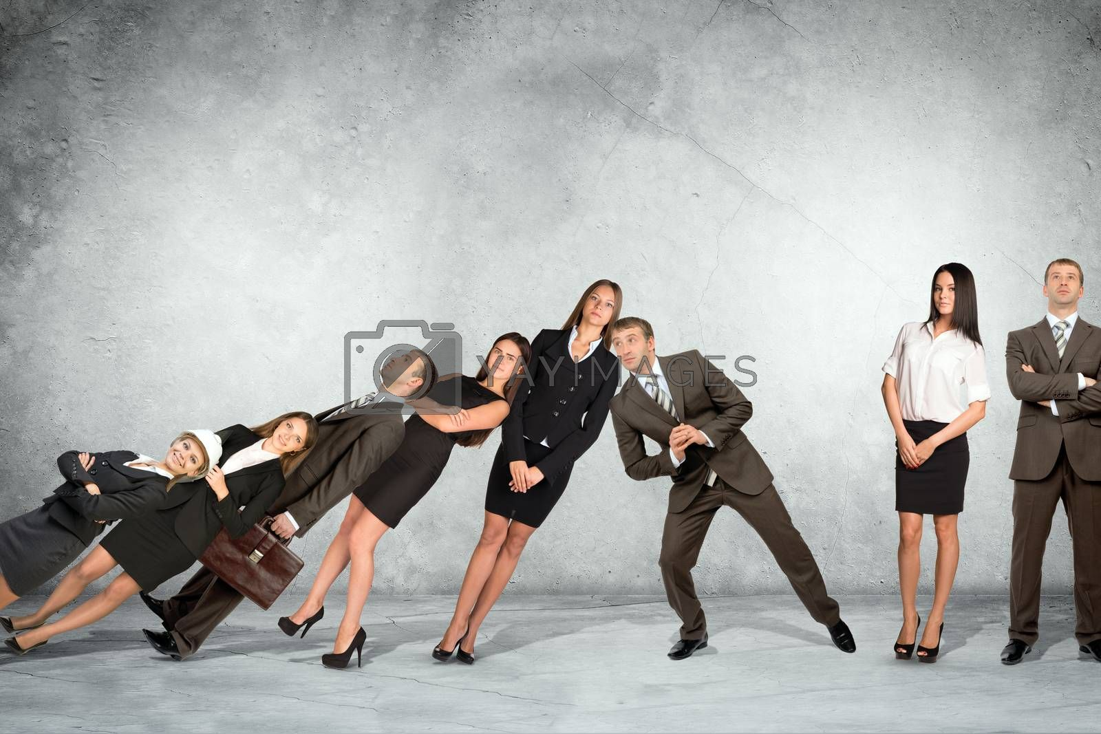 Businessman supporting falling people on grey wall background, co-working concept
