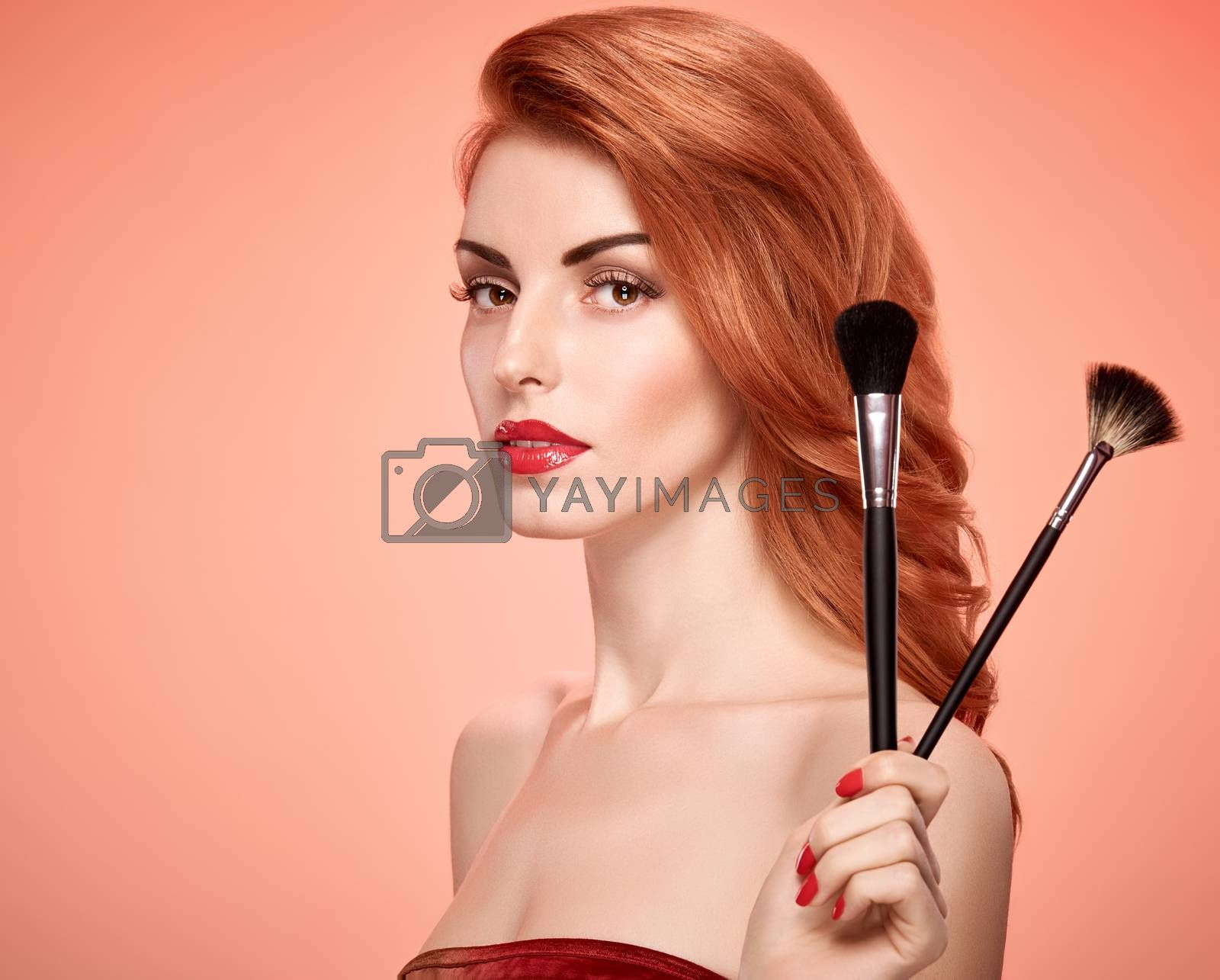 Beauty portrait nude woman eyelashes, perfect skin, red lips, fashion. Gorgeous sensual attractive pretty redhead sexy model girl with makeup brushes on pink, shiny wavy hair. People face, copyspace