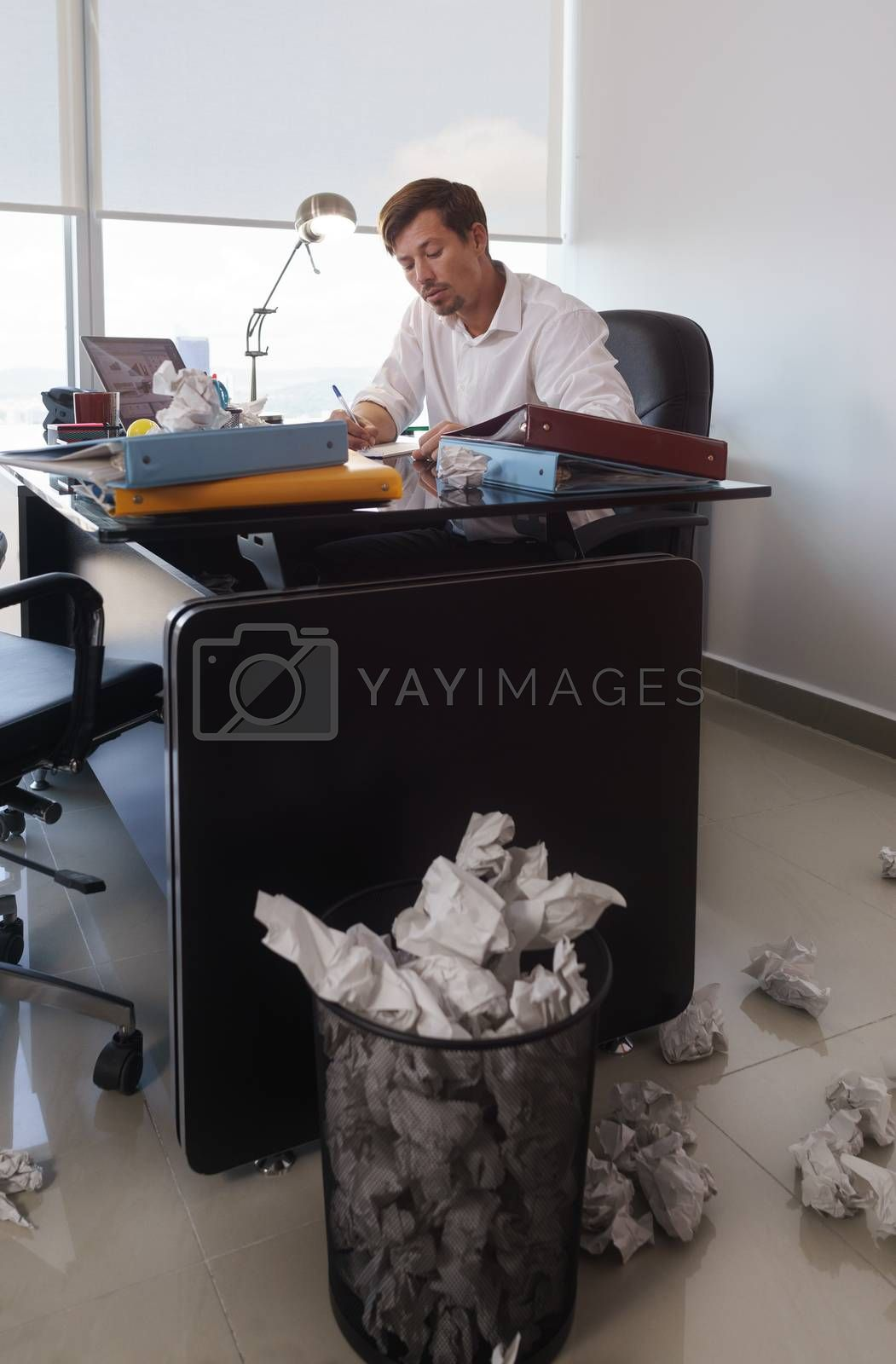 Corporate manager in modern office tries to write a job letter. The man is frustrated and keeps on throwing paper on desk and trash bin