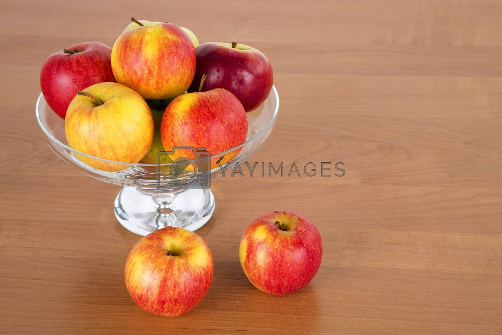 Fresh apples in the glass on a wooden background
