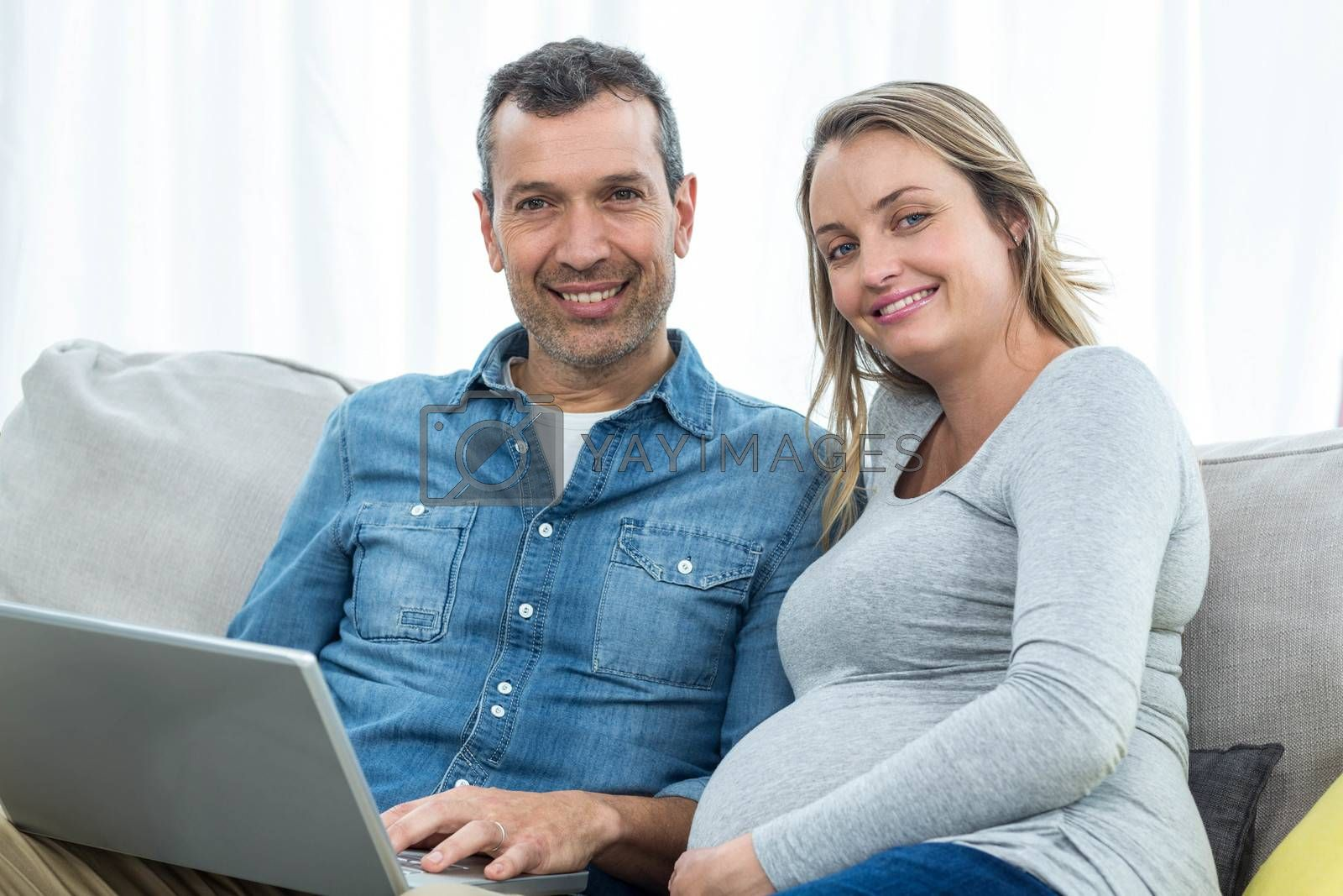 Portrait of couple sitting together on sofa and using laptop