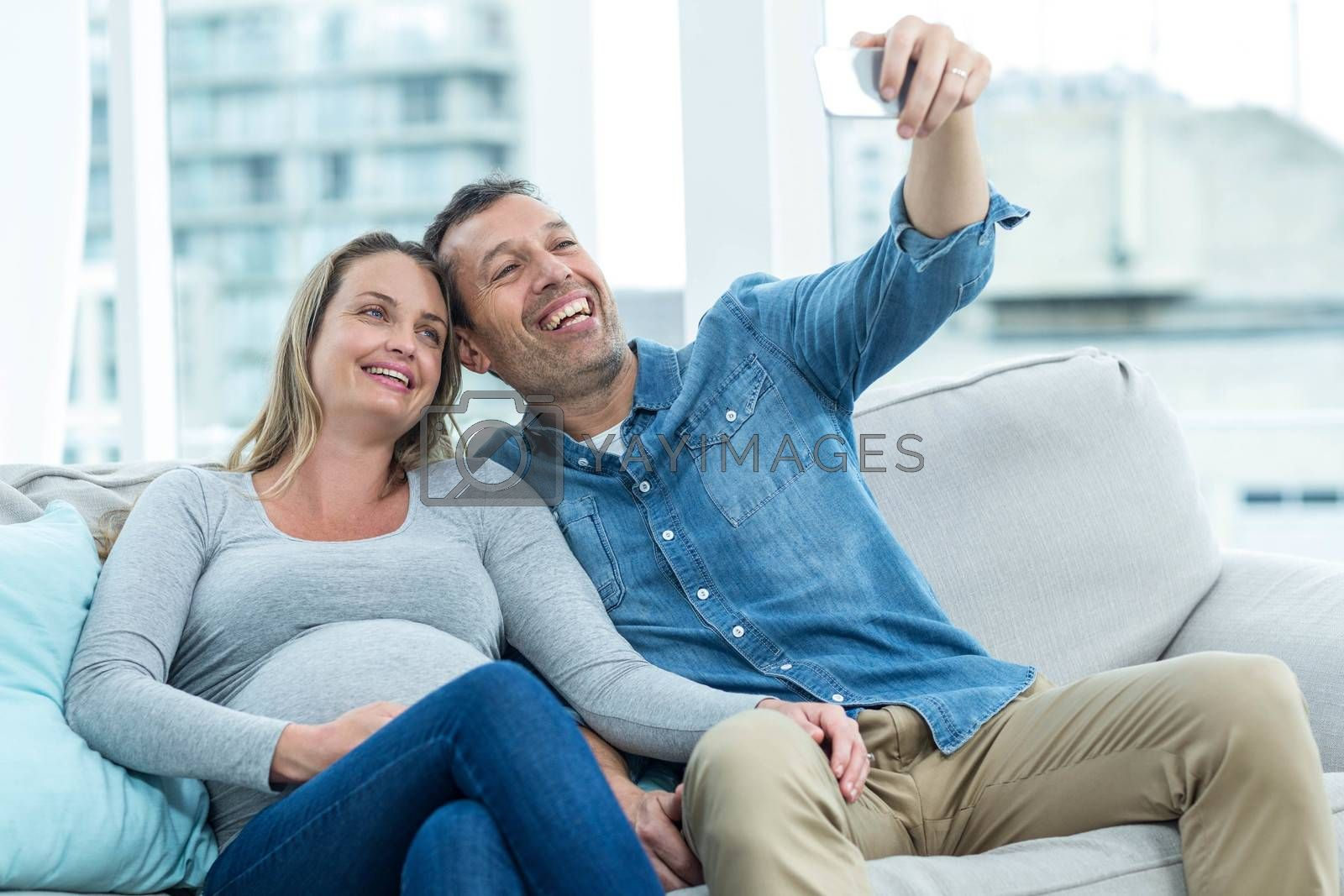 Couple sitting on sofa and taking a selfie on smartphone