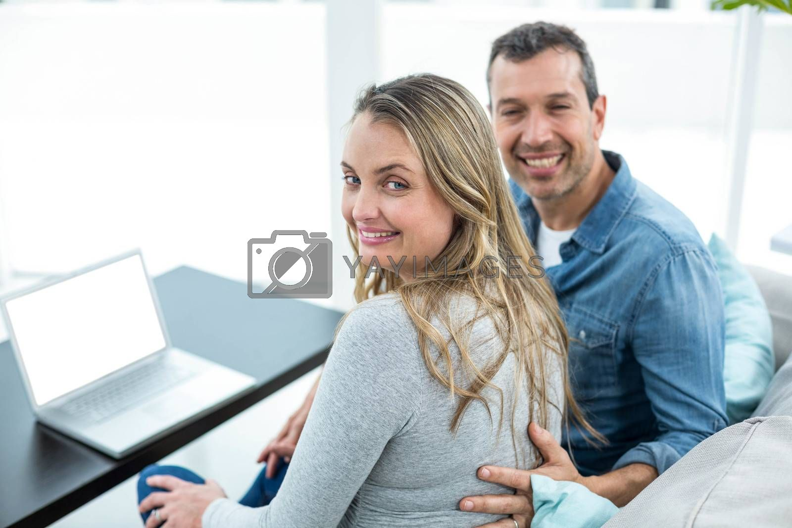 Portrait of couple sitting on sofa and using laptop in living room