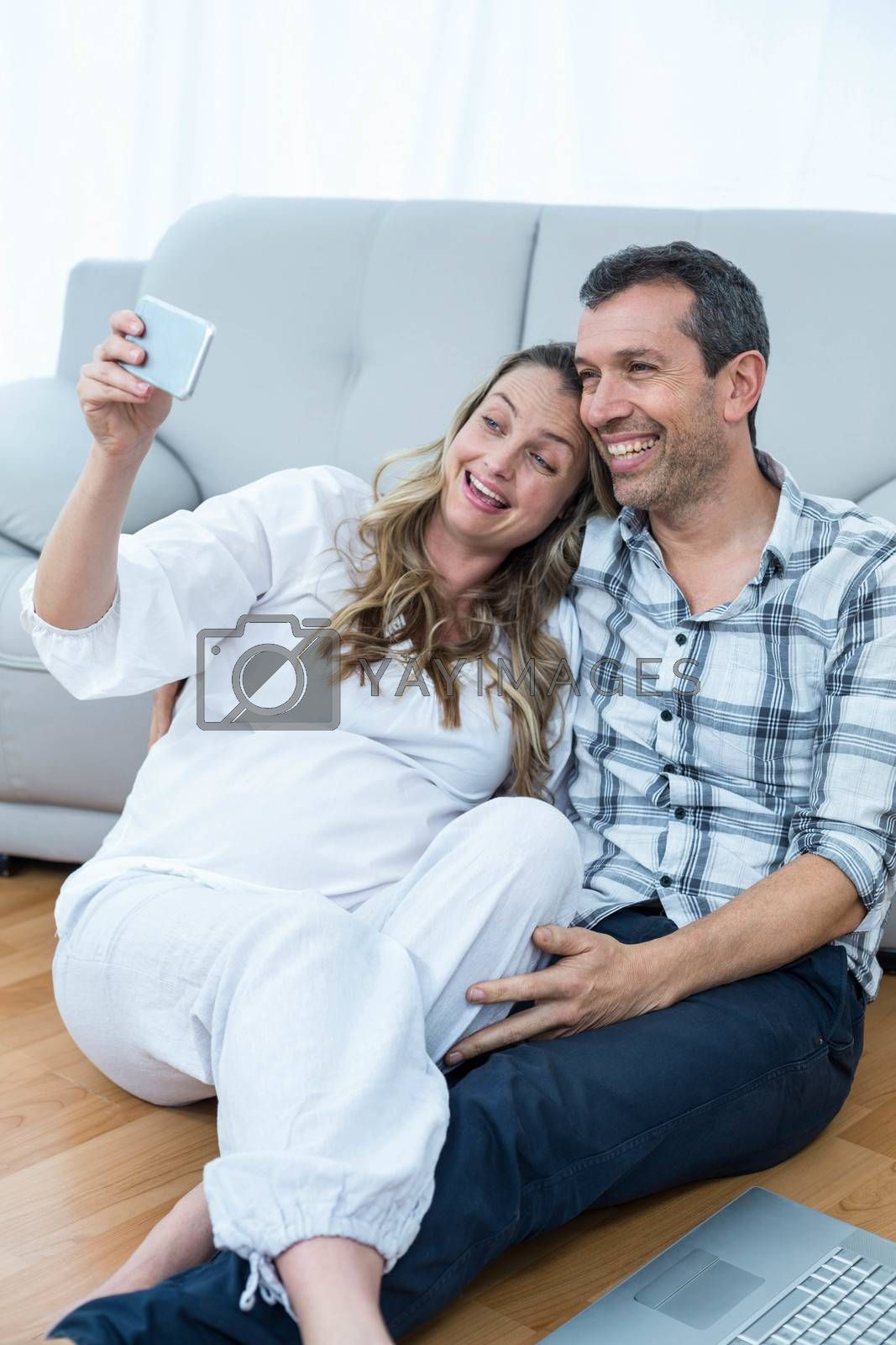 Pregnant couple sitting on floor using mobile phone in living room