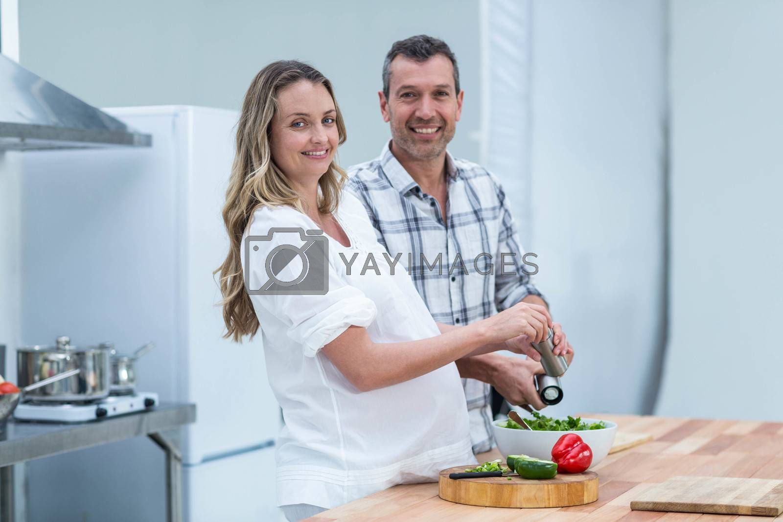 Portrait of pregnant couple preparing salad in kitchen