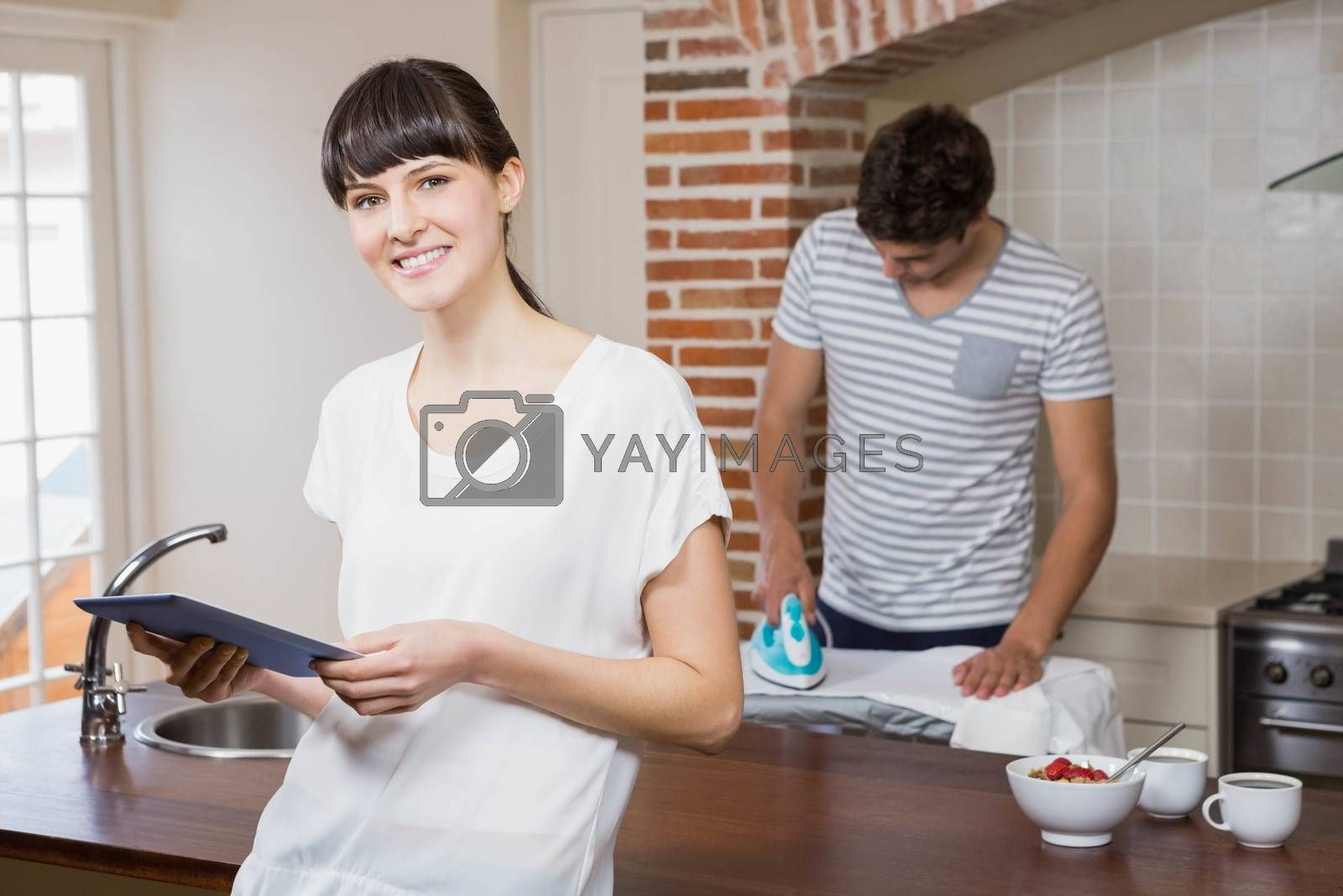 Woman using tablet in kitchen while man ironing a shirt in background