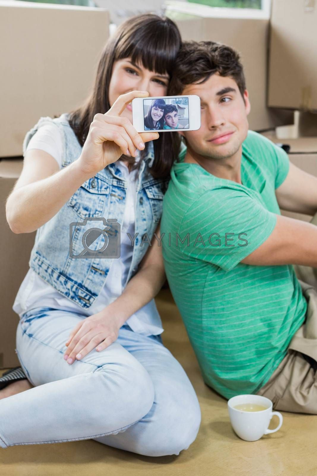 Young couple using mobile phone in their new house