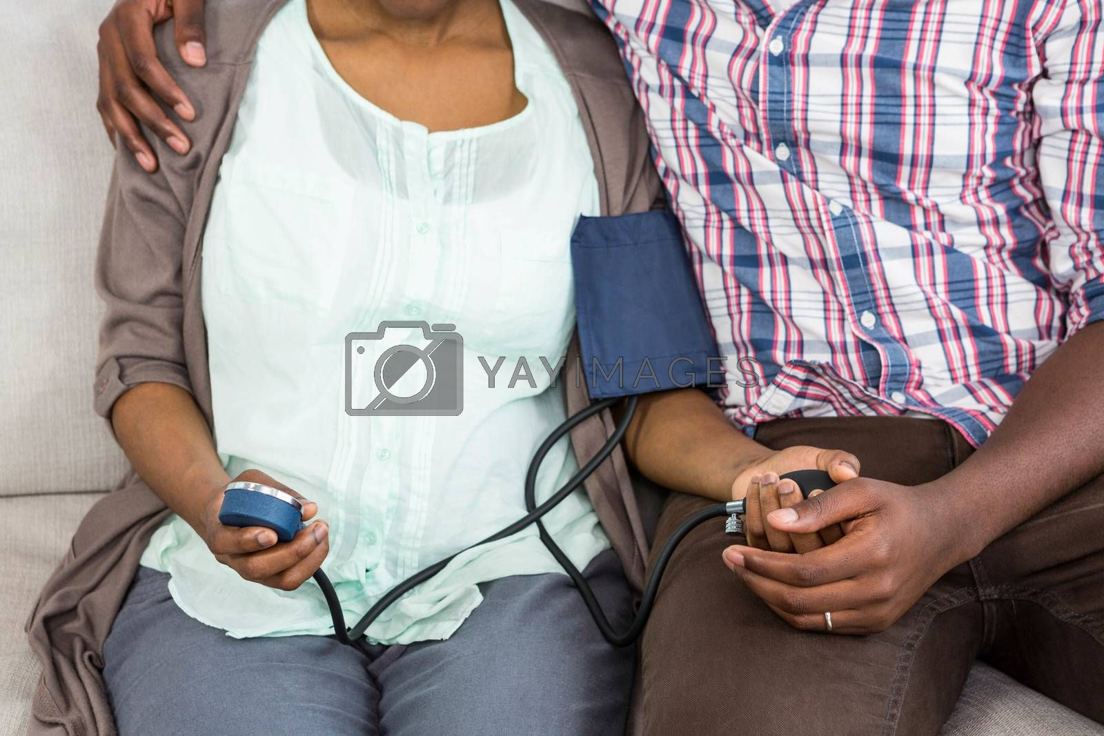 Woman checking blood pressure while sitting with man in living room at home