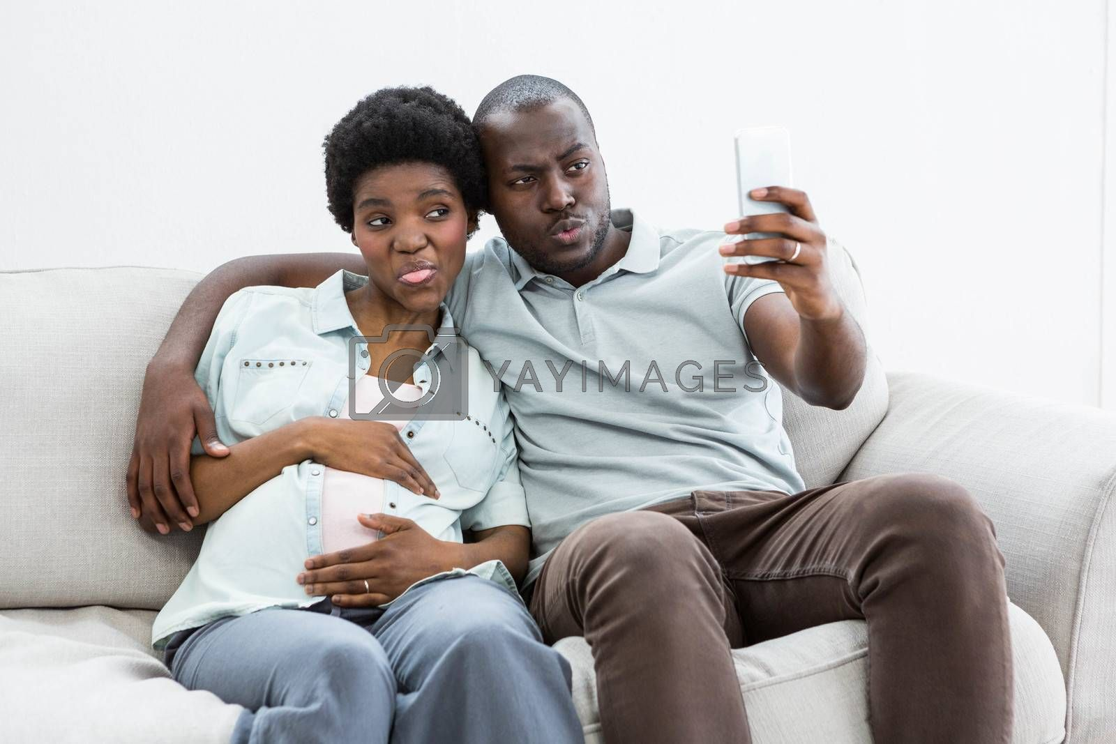 Pregnant couple taking a selfie on mobile phone at home