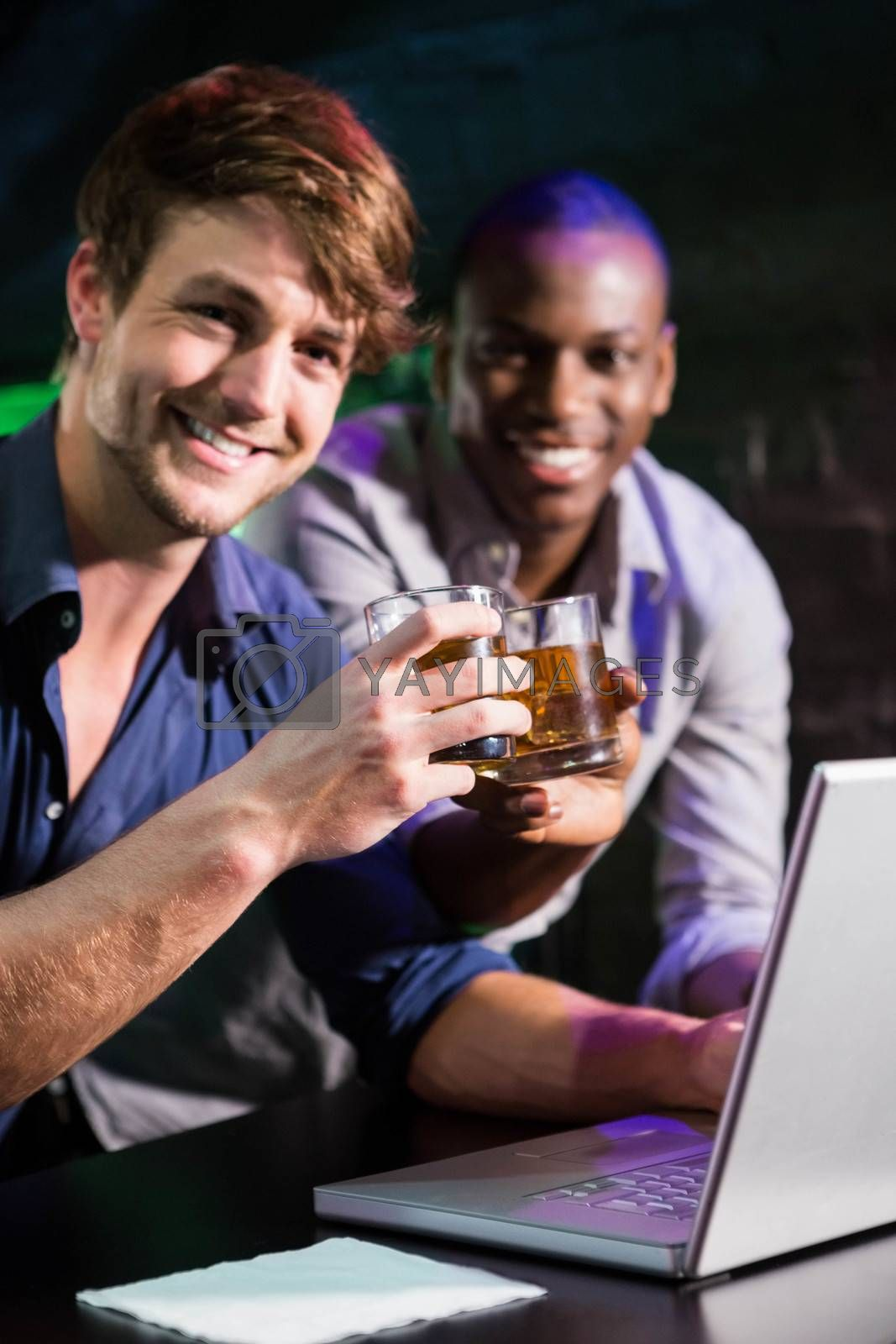 Two men toasting their whiskey glasses at bar counter while using laptop