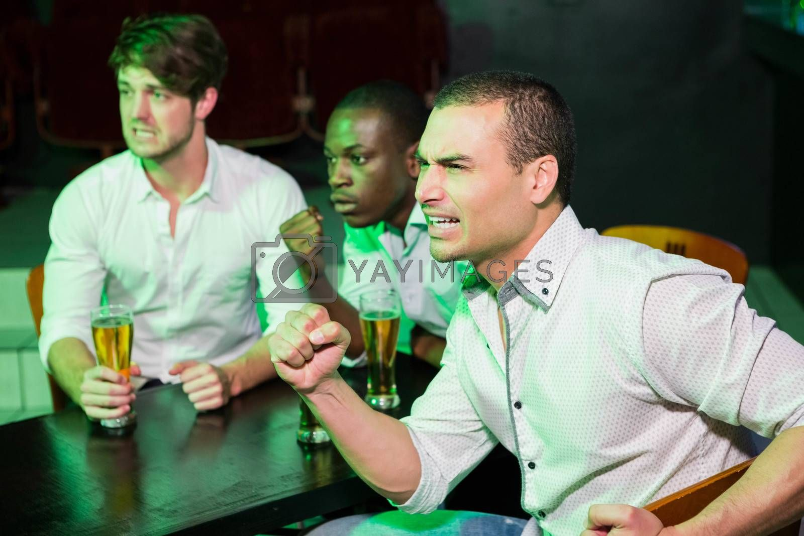 Group of anxious men watching television while having beer in bar