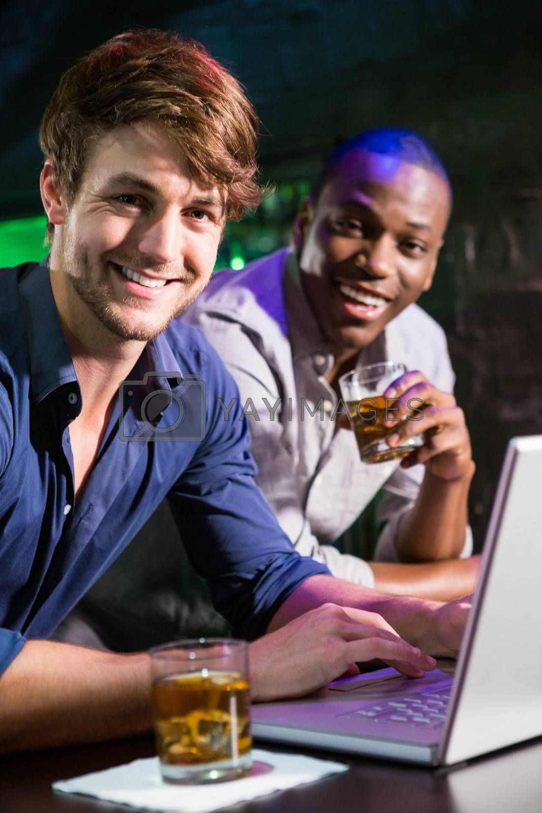 Two men having whiskey and using laptop at bar counter in bar